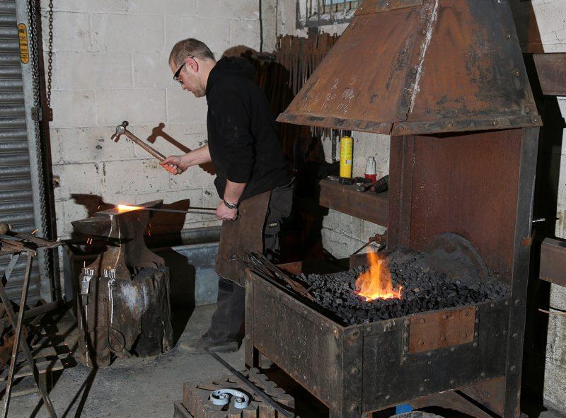 Steve at work forging iron scrolls for new balustrade panels